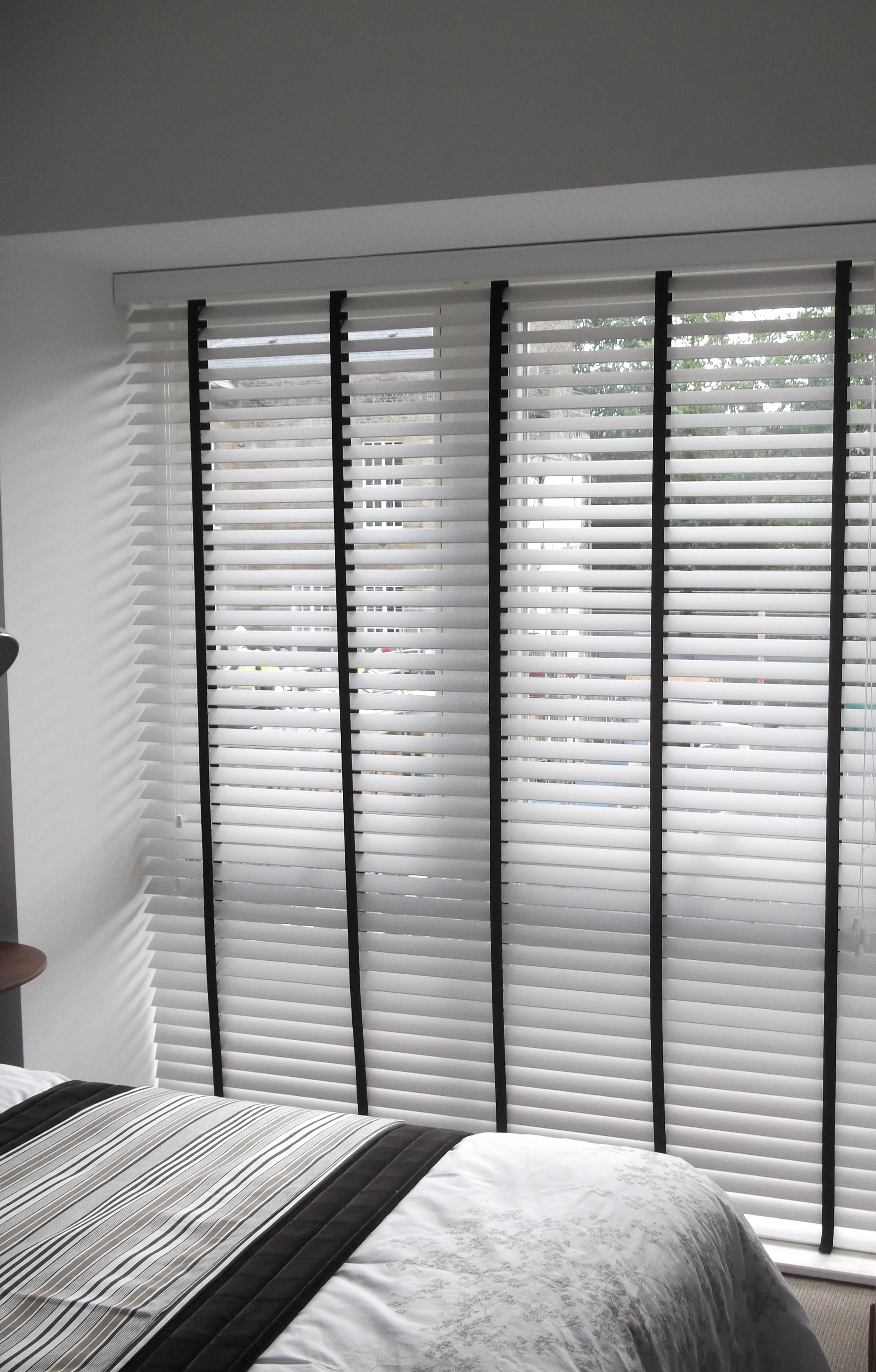 white wooden venetian blind with black tapes